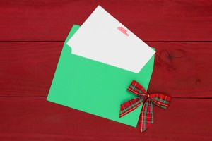 Christmas card letter with bow on red wooden background